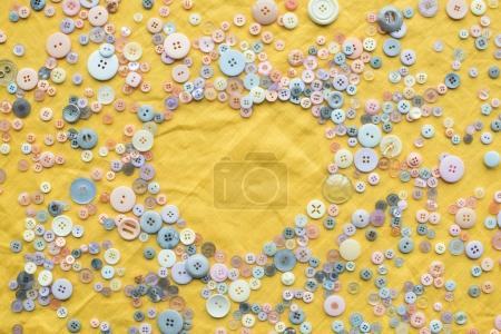 Photo pour Vue de dessus des boutons colorés cadre en forme de coeur sur fond de tissu jaune avec espace de copie - image libre de droit