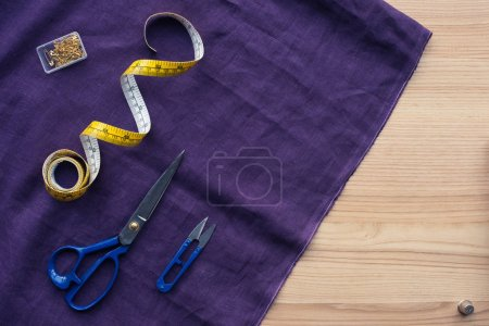 top view of purple fabric with sewing tools on table