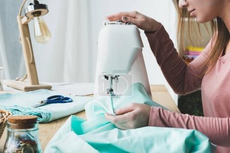 Photo pour Cropped image de jeune couturière à l'aide de machine à coudre au milieu de travail - image libre de droit