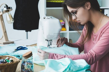 side view of young seamstress using sewing machine at workplace