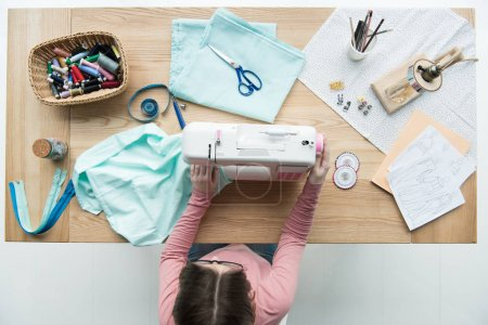 top view of woman seamstress at workplace with sewing machine