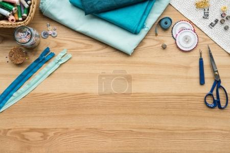 Photo for Top view of seamstress workplace on table with fabric, scissors and zip lockers - Royalty Free Image