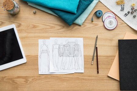 top view of seamstress workplace on table with fabric, tablet and sketches