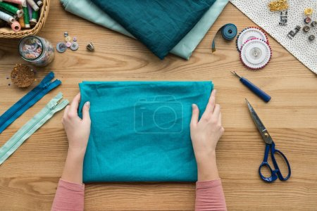 top view of cropped female hands folding fabric at seamstress workplace