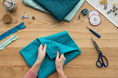 top view of cropped female hands folding fabric at seamstress workplace with scissors and buttons