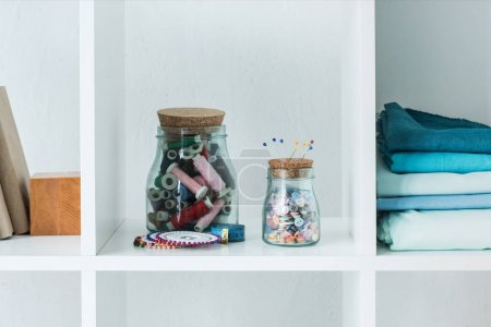 pile of folded colored fabric with stitchings in bottles on white shelf