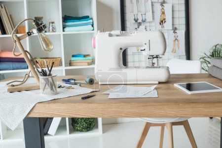 seamstress workplace with sewing machine on table