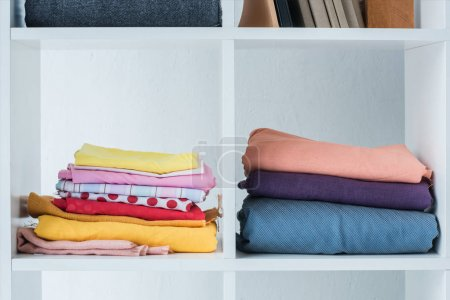 pile of folded colored fabric on white shelf