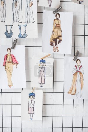 sketches of fashion outfit hanged on white checkered background