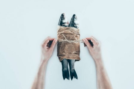partial view of hands wrapping sea fish in paper and tying with rope on grey