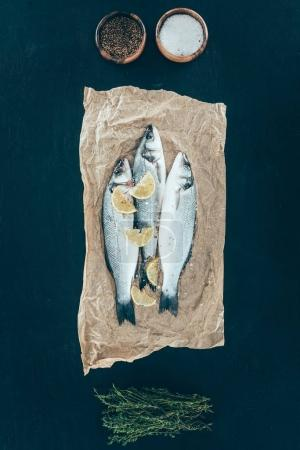 top view of healthy organic fish with lemon slices on baking paper on black