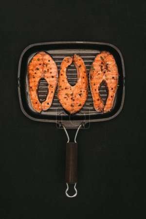 top view of grill with delicious salmon steaks isolated on black