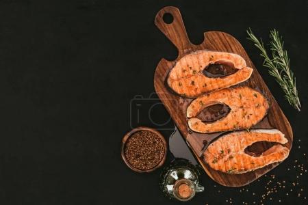 Photo pour Vue de dessus des steaks de saumon gastronomique sur planche à découper en bois avec des épices sur noir - image libre de droit