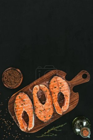 top view of salmon steaks on wooden cutting board with spices on black