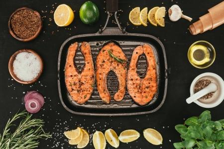 top view of salmon steaks on grill and spices on black