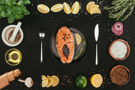 Photo for Top view of salmon steak with cutlery and seasonings on black - Royalty Free Image