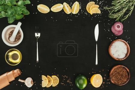 top view of cutlery and various spices and seasonings on black with copy space