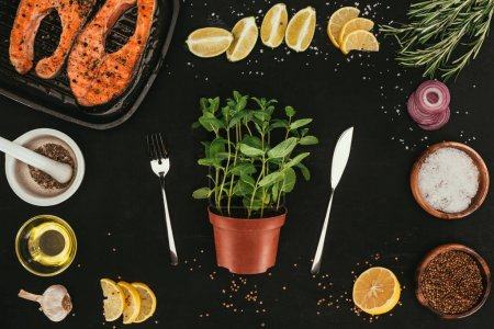 top view of mint in pot with fork and knife, salmon steaks and seasonings on black