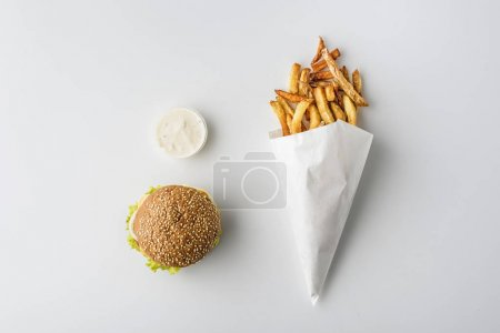 top view of french fries in paper cone, hamburger and mayonnaise, isolated on white