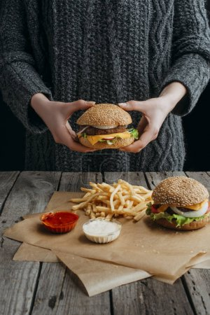 cropped view of woman holding cheeseburger and standig at table with french fries and sauces