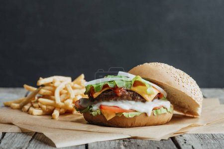 Photo for Traditional homemade burger on baking paper with french fries - Royalty Free Image