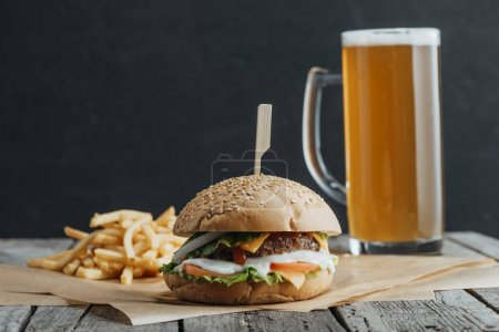 traditional homemade hamburger, french fries and glass of beer on baking paper on wooden table
