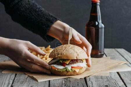 cropped view of female hands with hamburger, french fries and bottle of beer on baking paper on wooden table