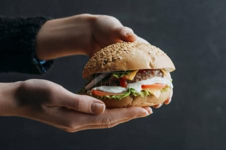 cropped view of female hands with traditional american homemade burger
