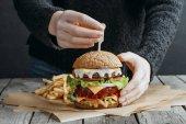 """Постер, картина, фотообои """"обрезанное мнение женской руки с большой вкусные чизбургер и картофелем на бумагу для выпечки"""""""