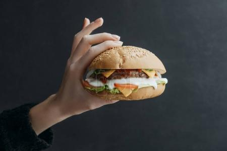 cropped view of hand with gourmet homemade cheeseburger on black
