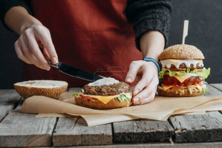 cropped view of girl in apron making tasty homemade cheeseburgers on baking paper on wooden tabletop