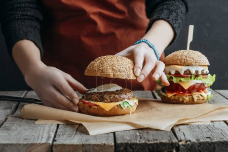 cropped view of girl in apron making homemade cheeseburgers on baking paper on wooden tabletop