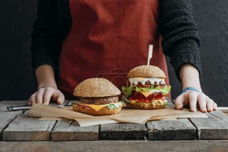 cropped view of girl in apron standing at wooden table with tasty cheeseburgers on baking paper