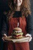 """Постер, картина, фотообои """"обрезанное вид девушка в фартук, холдинг деревянная доска с большой домашний чизбургер"""""""