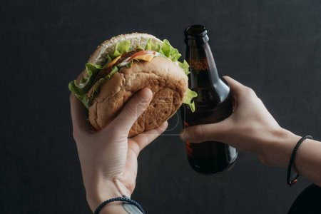 cropped view of person holding hamburger and bottle of beer
