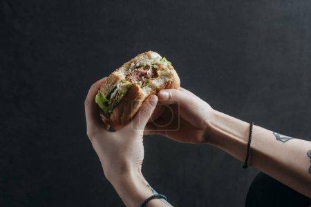 Photo pour Vue recadrée de la personne mangeant hamburger savoureux - image libre de droit