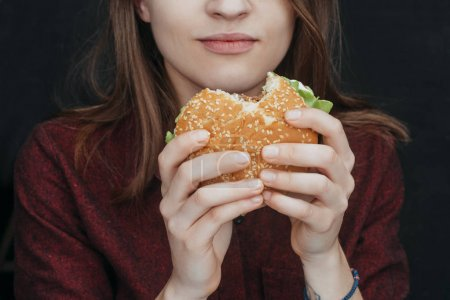 cropped view of girl eating tasty cheeseburger