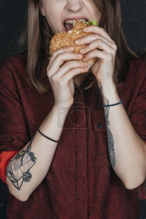 cropped view of tattooed girl biting tasty hamburger
