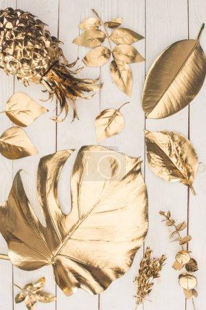 Photo pour Vue de dessus de l'ensemble de diverses feuilles dorées et l'ananas sur la surface en bois - image libre de droit
