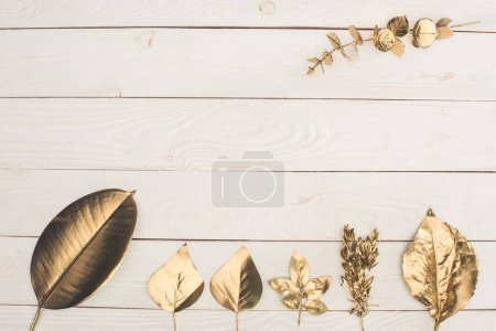 top view of set of different golden leaves on wooden tabletop