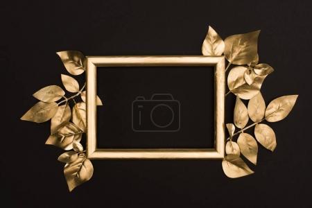 Foto de Vista superior del marco de fotos de oro y hojas aisladas en negro - Imagen libre de derechos