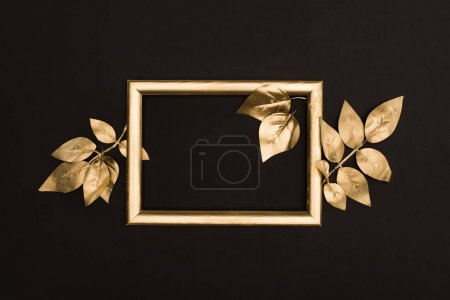 top view of golden photo frame and leaves isolated on black