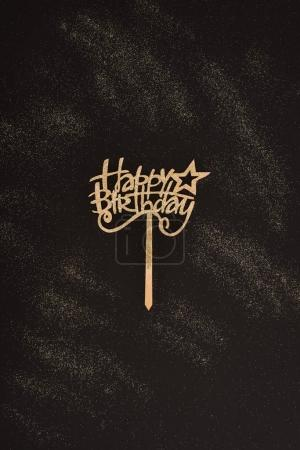 top view of golden happy birthday sign on black surface