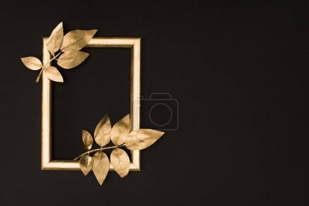 Photo for Top view of golden photo frame and leaves isolated on black - Royalty Free Image