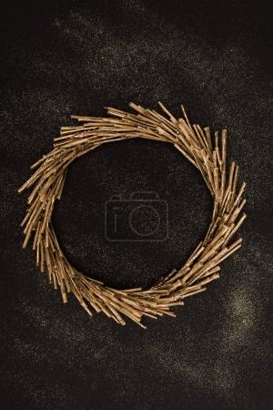 top view of golden wreath made of sticks on black surface