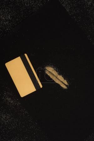 top view of golden credit card and powder lines isolated on black