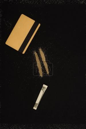 top view of golden credit card, dollar and powder lines isolated on black