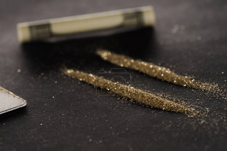 selective focus of golden powder lines and dollar on black surface