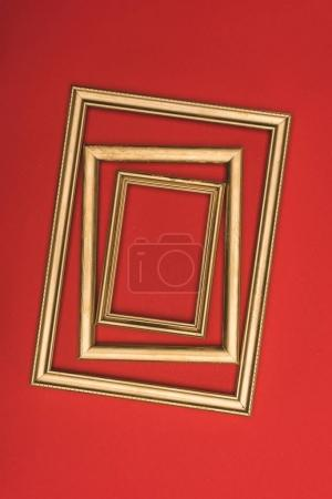top view of arranged of golden photo frames isolated on red