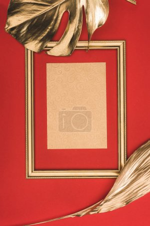 top view of golden photo frame, leaves and blank paper isolated on red